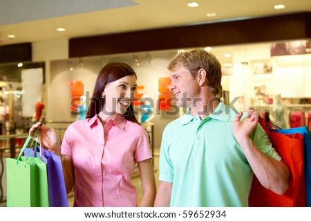 Portrait of pretty female and happy man looking at each other during shopping in trade center