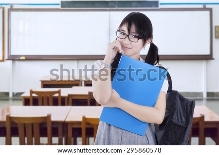 Portrait of pretty female college student holding folder while carrying backpack in the classroom