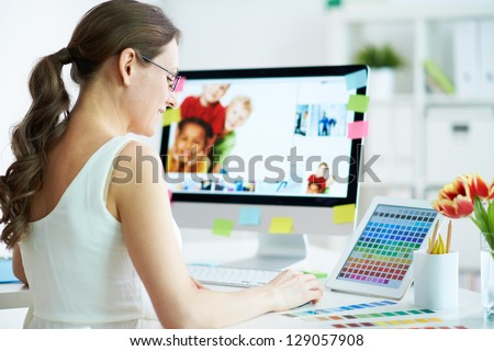 Portrait of pretty female designer working with colors at home - stock photo