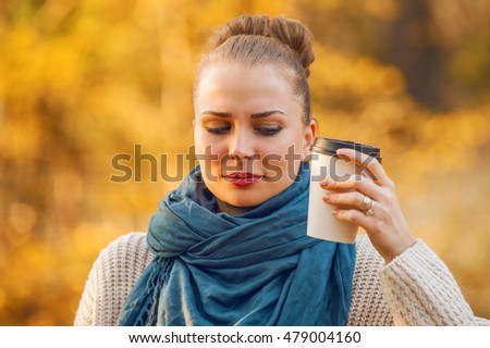 Portrait of pretty female holding almost empty cup of coffee