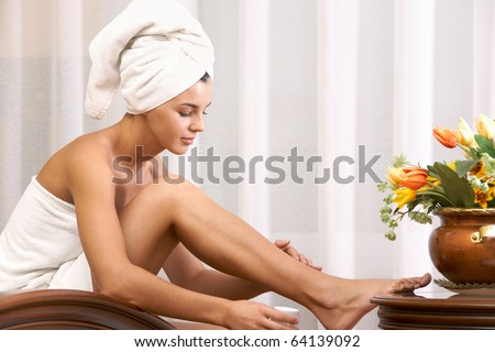 Portrait of pretty female taking care of her legs after bath - stock photo