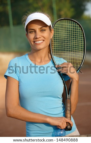 Portrait of pretty female tennis player standing on tennis court holding tennis racket, smiling.