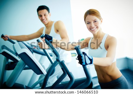 Portrait of pretty girl and young guy training on special sport equipment in gym - stock photo