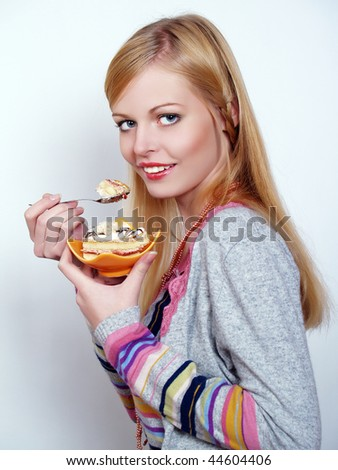 Portrait of pretty girl eating cake with pleasure