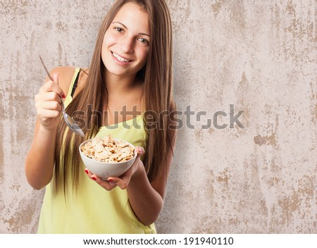 portrait of pretty girl eating cereals on a bowl - stock photo