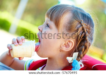 Portrait of pretty girl eating ice-cream outside - stock photo