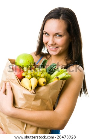 Portrait of pretty girl holding big paper sack in hands full of different fruits and vegetables