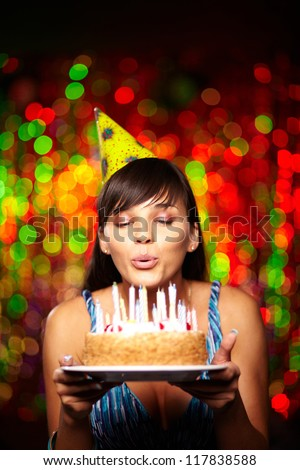 Portrait of pretty girl holding birthday cake and blowing candles at party - stock photo