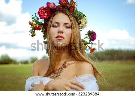 Portrait of pretty girl in flower wreath and ethnic necklace. Young woman with naked shoulders looking at camera on blurred countryside background. - stock photo