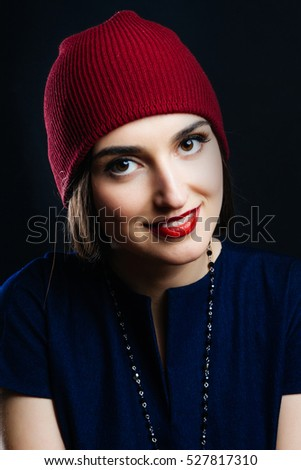 Portrait of pretty girl in red hat. She smiles and feels happy. Studio shot of a magnificent young woman in a fitting dress and elegant classic hat. Beauty, fashion concept.