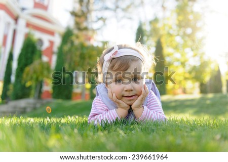 portrait of pretty girl laying in grass in sunlight - stock photo
