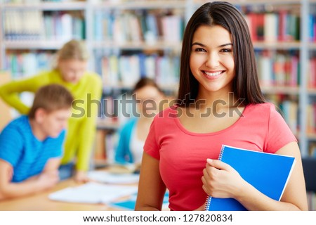 Portrait of pretty girl looking at camera in college library with her group mates on background - stock photo