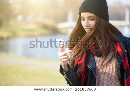 Portrait of pretty girl outdoor, wearing a cap talking on a cell phone - stock photo