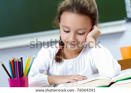 Portrait of pretty girl reading at workplace - stock photo