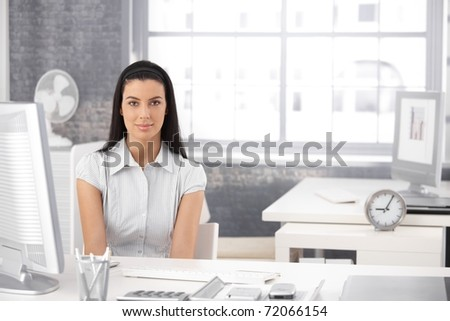 Portrait of pretty girl sitting at desk in bright office, smiling at camera.? - stock photo
