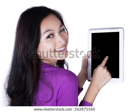 Portrait of pretty girl smiling at the camera while touching a tablet screen, isolated over white - stock photo