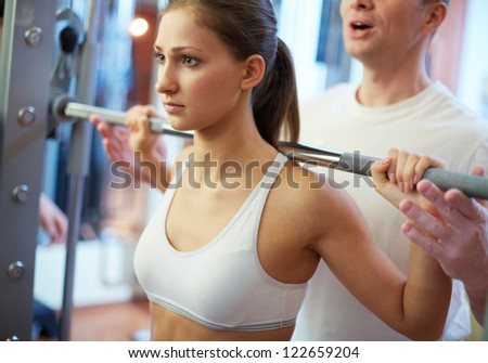 Portrait of pretty girl training in gym with her trainer helping her - stock photo