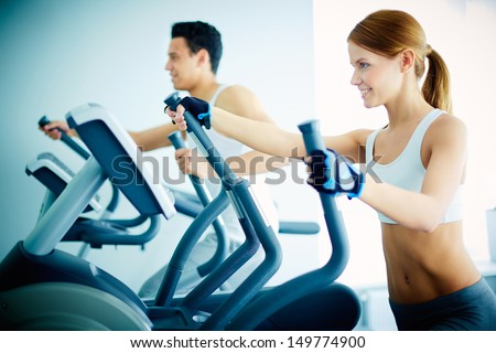 Portrait of pretty girl training on special sport equipment in gym - stock photo