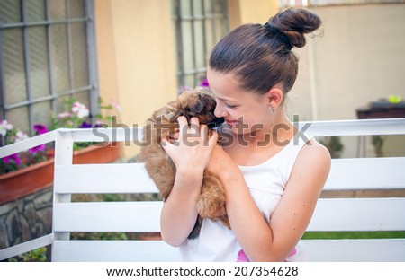 Portrait of pretty girl with a pekinese puppy - stock photo