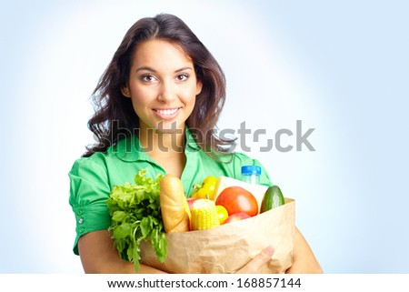 Portrait of pretty girl with big paper sack full of different fruits and vegetables in isolation - stock photo
