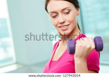 Portrait of pretty girl with dumbbell doing exercise in gym - stock photo
