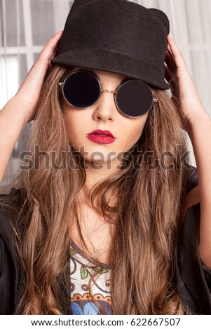 Portrait of pretty girl with long hair and red lips wearing glasses and bowler-hat.
