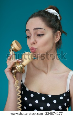 Portrait of pretty girl with retro phone in blue background