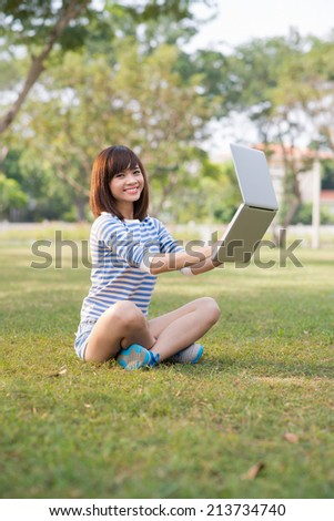 Portrait of pretty girl working on laptop floating in the air
