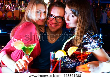 Portrait of pretty girls embracing happy guy and looking at camera at party - stock photo