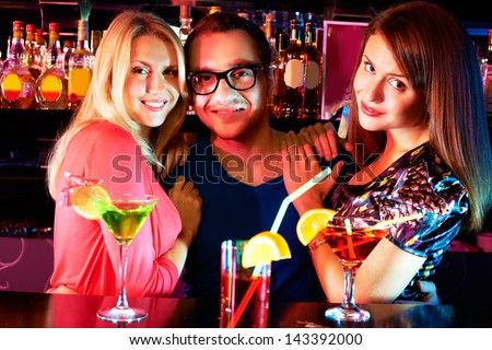 Portrait of pretty girls embracing happy guy and looking at camera at party