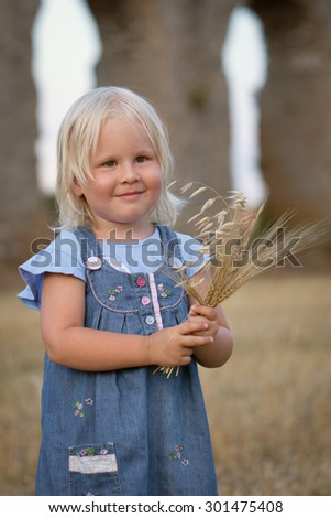 Portrait of pretty happy cheerful little girl on background of haystacks - stock photo