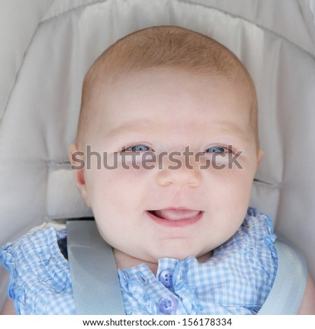 Portrait of pretty happy little baby girl in blue dress sitting in car seat - stock photo