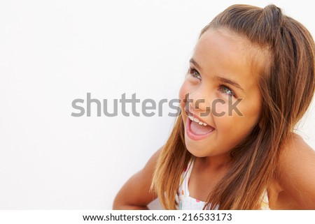 Portrait Of Pretty Hispanic Girl Standing By Wall