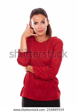 Portrait of pretty hispanic lady on red shirt with calling gesture and funny face looking at you while standing on isolated studio