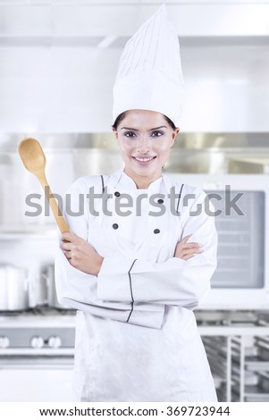 Portrait of pretty indian chef standing in the kitchen while holding spoon and wearing uniform