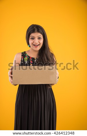 Portrait of pretty indian girl holding a box, asian girl holding box, isolated over yellow background - stock photo