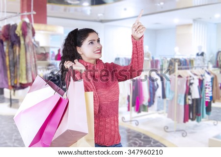 Portrait of pretty indian woman pointing at copy space in the shopping center while carrying shopping bags and wearing winter clothes - stock photo