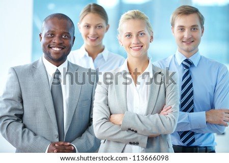 Portrait of pretty leader looking at camera with three partners behind