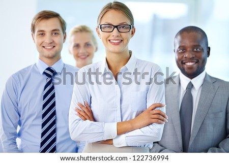 Portrait of pretty leader looking at camera with three partners behind - stock photo