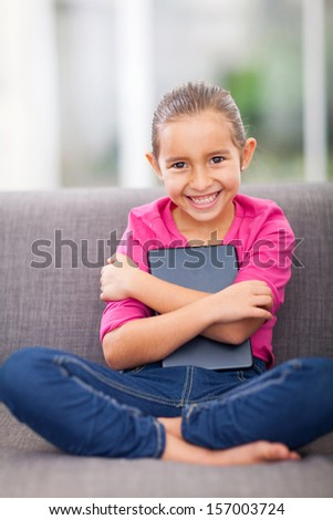 portrait of pretty little girl holding tablet pc on sofa at home - stock photo