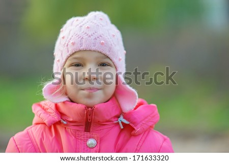 Portrait of pretty little girl in red jacket in autumn park.