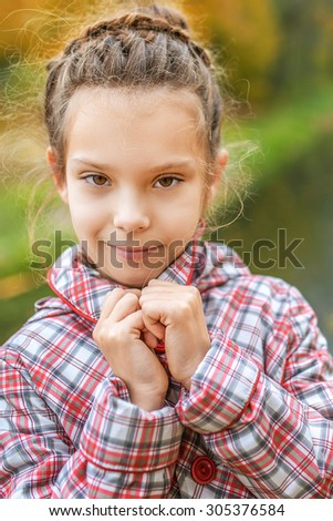 Portrait of pretty little girl in red jacket in autumn park. - stock photo