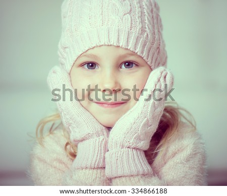 Portrait of pretty little girl in rose hat and gloves at christmas time