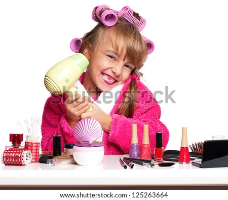 Portrait of pretty little girl seating at table with makeup accessories on white background - stock photo