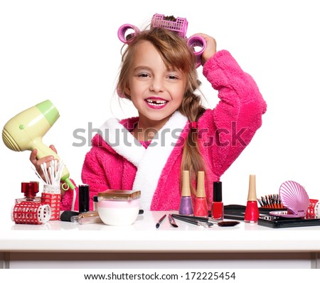 Portrait of pretty little girl seating at table with makeup accessories, on white background  - stock photo