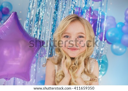 Portrait of Pretty little girl sits in a studio with a lot of balloons and holds a hair - stock photo