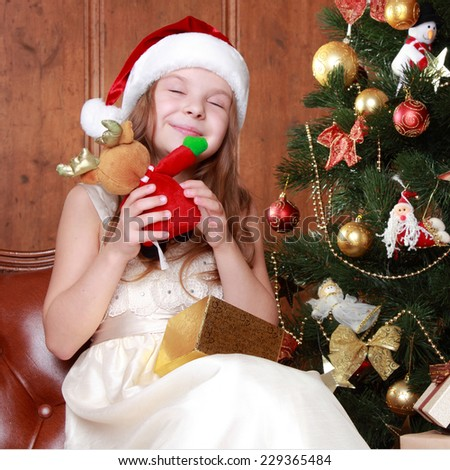 Portrait of pretty little girl with christmas present smiling - stock photo