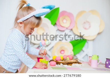Portrait of pretty little girl with Easter eggs, big paper flower decor as a background - stock photo