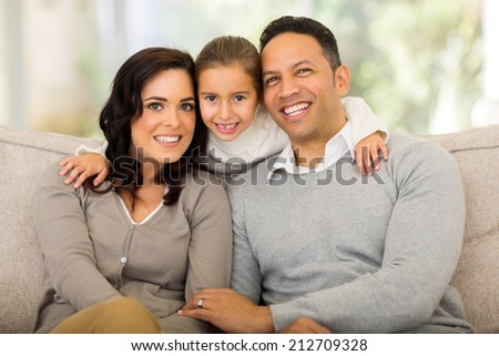 portrait of pretty little girl with her parents at home - stock photo