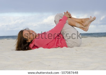 Portrait of pretty looking mature woman exercising at beach, keeping healthy and fit, isolated with ocean and dark storm clouds as background and copy space. - stock photo